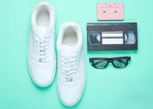 80s, retro style. White hipster sneakers, audio and video cassette, 3D glasses on a mint-colored paper background. Top view stock photos