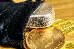It`s the right time to buy precious metals, gold and silver. Closeup of golden coins and silver brick falling out of black moneybag and laying on wooden stock photography