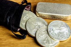 It`s the right time to buy precious metals, gold and silver especially. Closeup of silver coins american one ounce eagles and brick falling out of black money stock photo