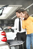 It?s so roomy inside. Handsome young car salesman showing the ca Stock Photography