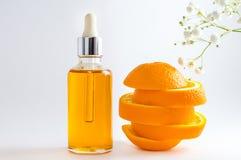 S?rum de vitamine C dans la bouteille cosm?tique avec le compte-gouttes, l'orange coup?e en tranches et les fleurs sur le fond bl photographie stock