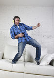 20s or 30s man jumped on couch listening to music on mobile phone with headphones playing air guitar Royalty Free Stock Image