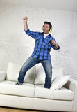 20s or 30s man jumped on couch listening to music on mobile phone with headphones playing air guitar. Young attractive 20s or 30s man having fun jumped on home stock photo