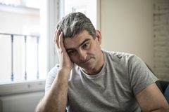 Sad and worried man with grey hair sitting at home couch looking. 40s or 50s sad and worried man with grey hair sitting at home couch looking depressed and Stock Photos