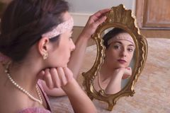 1920s scene with mirror. Sensual young woman in 1920s flapper dress and headband looking in an antique mirror stock images
