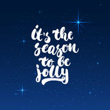 It`s the season to be jolly - lettering Christmas and New Year holiday calligraphy phrase isolated on the shining. It`s the season to be jolly - lettering stock illustration