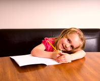 It's A Secret. Young blond girl writing something in a notebook and shielding it with her hand Stock Photos