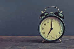 It`s seven o`clock already, time to wake up for breakfast, vintage old black metallic alarm clock Stock Image