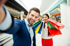 It`s shopping and fun time. Cute selfie portrait of cheerful  su. Ccessful happy young lovely couple holding  colored shopping bags and laughing in mall at Royalty Free Stock Photo