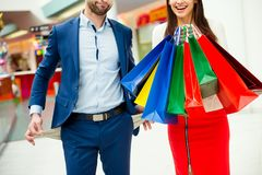 It`s shopping and fun time! Photo of young cheerful couple in a. Mall, men showing his emrty pockets, women happy women holding a lot of bags. Concept of Stock Images