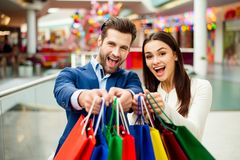 It`s shopping and fun  time. Portrait of cheerful  successful ha. Ppy young lovely couple holding  colored shopping bags and laughing in mall. Concept of Royalty Free Stock Photo