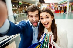 It`s shopping time with crazy sales and fun. Selfie portrait of. Cheerful  successful happy young lovely couple surprised holding  colored shopping bags and Stock Photography