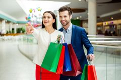 It`s shopping time with  sales and fun. Cute cheerful  successfu. L happy lovely couple in jacket holding colored shopping bags, pointing on shop  and laughing Stock Image