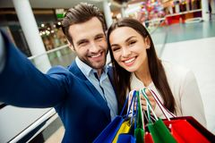 It`s shopping time with  sales and fun. Cute selfie portrait of. Cheerful  successful happy young lovely couple in jacket surprised holding  colored shopping Royalty Free Stock Image