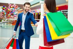It`s shopping time with  sales and fun. Handsome cheerful  succe. Ssful happy  men in jacket holding hands and following his lovely women with colored shopping Royalty Free Stock Images