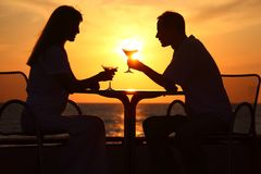 's silhouettes on sunset sit at table Royalty Free Stock Photography