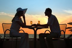 's silhouettes on sunset sit with two glasses Royalty Free Stock Images