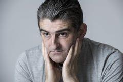 40s 50s smutny i zmartwiony mężczyzna patrzeje udaremniający i rozważny w twarzy wyrażeniu odizolowywającym na popielatym zmartwi zdjęcie stock