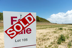 Its Sold. Image of a for sale sign on vacant land covered with a sold sign against a lovely blue sky. Copyspace royalty free stock photos
