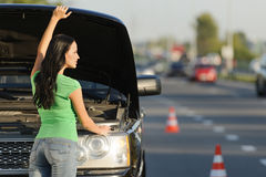 It's something wrong with my car. An attractive young Caucasian woman standing in front of her broken car with the hood open Royalty Free Stock Image