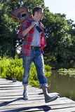 40s sorridenti equipaggiano la chitarra della tenuta nella camminata vicino all'acqua Immagini Stock