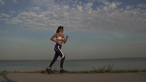 20s sporty female warms up and starts running on the waterfront. Girl athlete running along the seafront at the beach at. Portrait of a sportswoman running on stock video