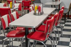 50s style diner with red and white chairs. 50s style diner with black and white tile floor, red vinyl chairs, and laminate and chrome tables Stock Photo