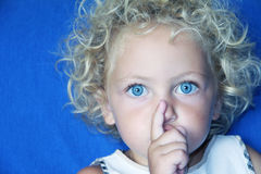 It's a surprise. A young caucasian child with blue eyes making a gesture with her finger to be quiet Royalty Free Stock Image