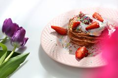 S?ta pannkakor med jordgubbar, keso och f?rgrika sockerst?nk arkivbild