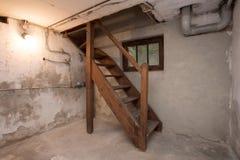 S?tano vac?o en el edificio industrial viejo abandonado con poca luz y escaleras de madera fotografía de archivo libre de regalías