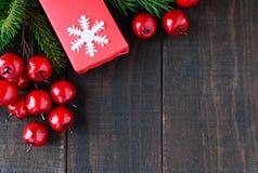 ` S, tema del Año Nuevo de la Navidad Cajas de regalo, baya en fondo de madera oscuro Foto de archivo libre de regalías