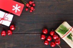 ` S, tema del Año Nuevo de la Navidad Cajas de regalo, baya en fondo de madera oscuro Fotografía de archivo