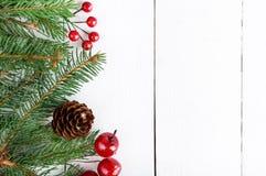 ` S, tema del Año Nuevo de la Navidad El abeto verde ramifica, las bayas decorativas en el fondo de madera blanco Fotos de archivo libres de regalías