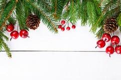 ` S, tema del Año Nuevo de la Navidad El abeto verde ramifica, las bayas decorativas en el fondo de madera blanco Foto de archivo