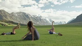 Trendy Hipster Girls having fun outdoor. Three cute women are whirling on green grass. Best friends. stock video footage