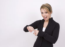It's Time. A pretty young woman points to her watch and is pleased that it's time. For what Stock Photo