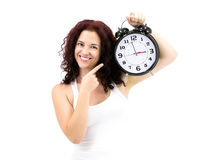It's Time for... Adorable Smilling Young Woman holding huge heavy retro style clock. Studio shot on white background Stock Image