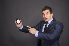 It's Time!. Businessman holds out alarm clock. Focus on alarm clock Royalty Free Stock Photo