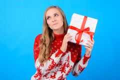 It`s time for giving presents to everyone! Your happy cute girl. Wants to open a giftbox she found it under an evergreen tree in the morning. She is wearing Royalty Free Stock Images