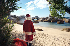 It's about time Santa got some sunshine!. Father Christmas standing on a tropical beach admiring the view Royalty Free Stock Photography