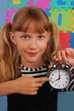 It`s time for school. Schoolgirl pointing retro alarm clock and showing that it`s time for school Stock Photography