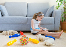 It's time to clean up your toys!. Little girl playing with tablet pc, don't want to do the cleaning Stock Photography