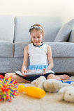 It's time to clean up your toys!. Little girl playing with tablet pc, don't want to do the cleaning Stock Photo