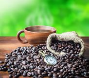 It`s time to coffee, Coffee bean heap on wood floor with hemp ba. Gs and coffee cup, green nature background Stock Photography