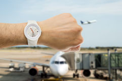 It's the time to departure flight. Hand with wristwatch with airport in the background as the concept of punctuality in the transport royalty free stock image