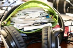 Time to do expense reports - a green zippup pouch full of receipts sitting in the circle of a headphone on messy desk. It,s time to do expense reports - a green Stock Images