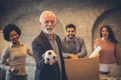 It`s time to get out of business. It`s to get out of business. Businesspeople in the office. Man holding football ball. on man stock image