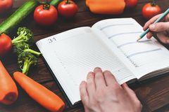 A man writes a diet plan. The concept of diet. Dietary Menu royalty free stock photography