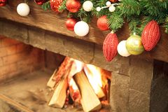 New Year / Christmas tree with colorful festive decorations on the fireplace Royalty Free Stock Image