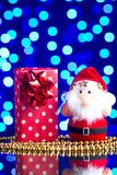 Santa Claus toy, gift in package and golden beads on a glass table with a beautiful blue bokeh Stock Images